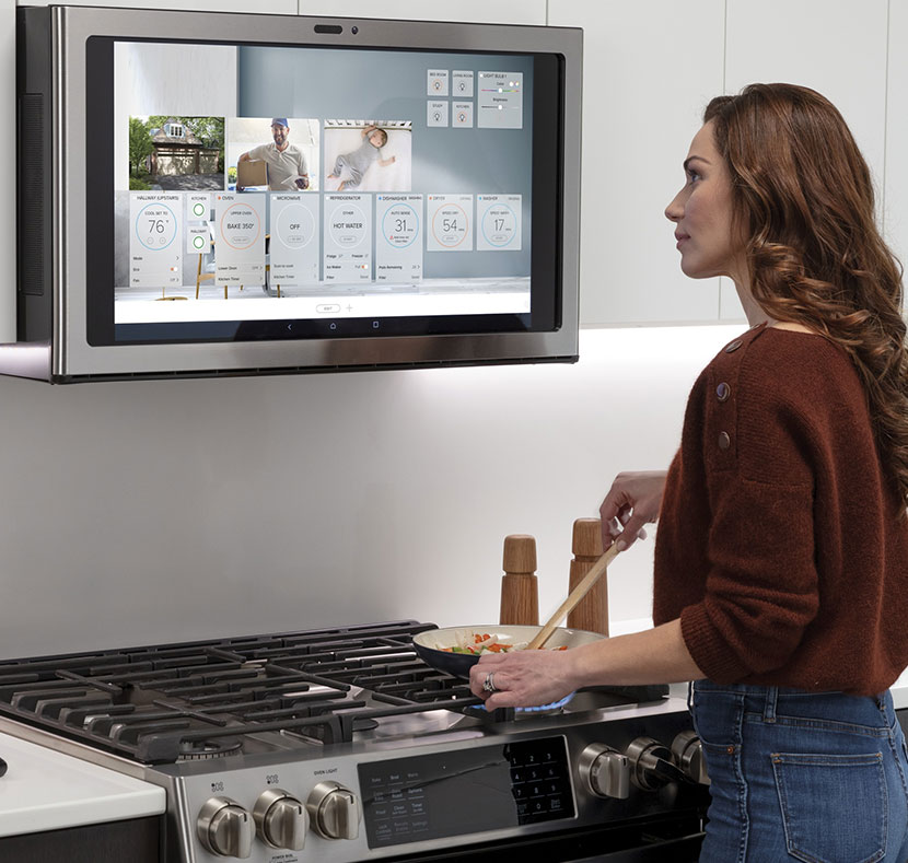 Woman looking at GE Profile Kitchen Hub recipe directions while cooking.